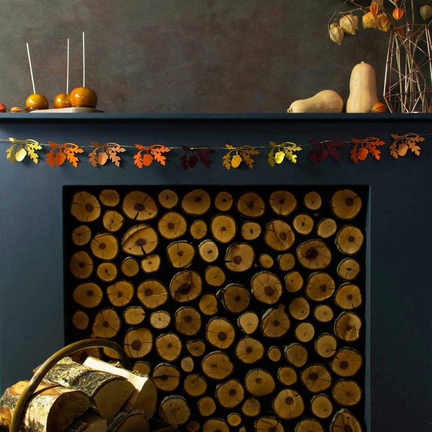 Chimenea decorada para otoño con guirnalda de hojas.