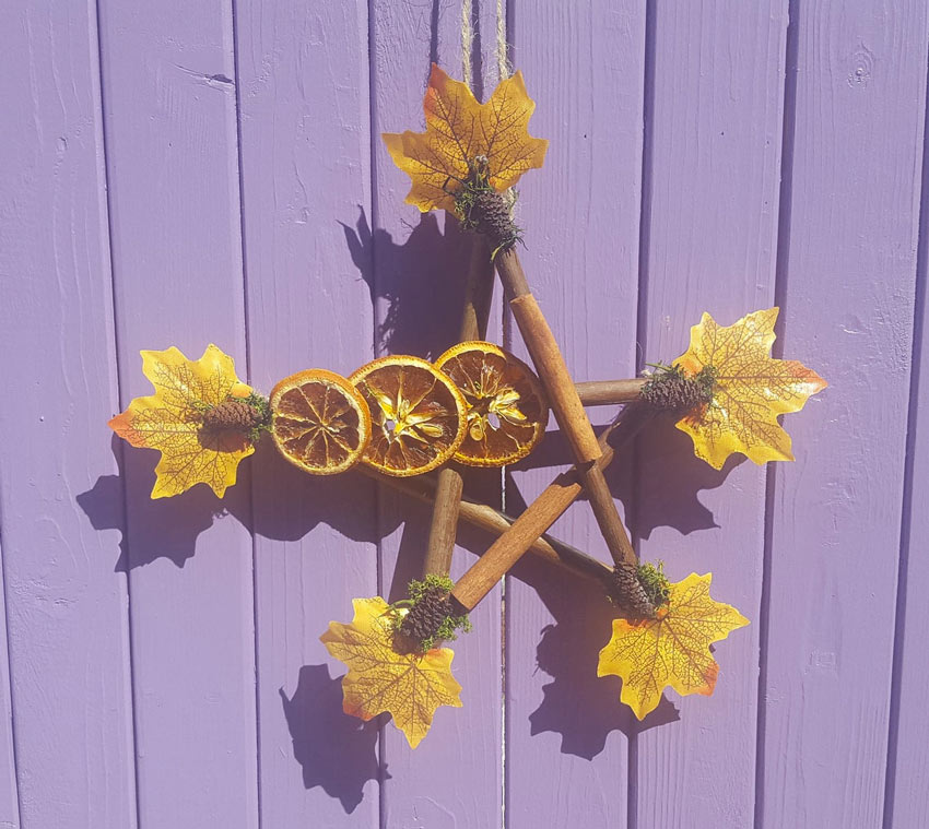 Decoración otoñal realizada con palos y frutos secos.